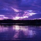 Vivid mauve cloudy Sunrise Seascape Australia. An inspirational Mauve colored cloudy sunrise seascape over sea water with water reflections. Queensland Royalty Free Stock Photography