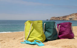 Vivid multicolored beach bags on the seashore Royalty Free Stock Photography