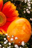 Vivid orange Easter egg with a gerbera and rose Royalty Free Stock Photo