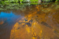 Vivid orange rocks underwater. Vivid orange rocks underwater at Kangaroo river, NSW, Australia royalty free stock photo