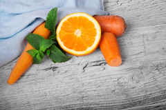 Vivid orange, slices of carrot and sappy green leaves of mint on a light wooden background. Royalty Free Stock Images
