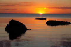 Vivid orange sunset over water, with rock silhouettes Stock Photo