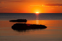 Vivid orange sunset over water, with rock silhouettes Royalty Free Stock Image