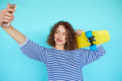 Vivid portrait of hipster young woman with skateboard royalty free stock image