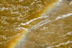 Vivid rainbow across churning muddy river. Stock Images
