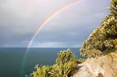 Vivid rainbow over Mount. Vivid rainbow bridge over pathway Mount Maunganui New Zealand stock image