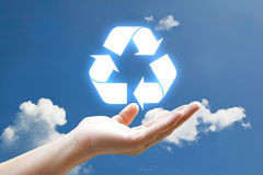 Vivid recycle icon. Hand and vivid recycle icon on sky Royalty Free Stock Photo
