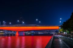 Vivid red illumination of bridge in night. Super bright red neon illumination of bridge in night time, Brisbane stock images