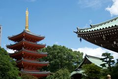 Vivid red pagoda in Fukuoka, Japan. Glowing golden spire and green trees; rooftops in foreground royalty free stock photo
