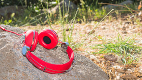 Vivid red wired headphones on the stone Royalty Free Stock Photo