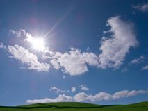 Vivid sky and field showing sun and clouds Royalty Free Stock Photography