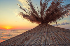 Vivid sunrise on a beautiful beach with sunshade Royalty Free Stock Photography
