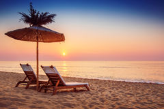 Vivid sunrise on a beautiful sandy beach and sunshade royalty free stock images