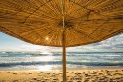 Vivid sunrise on a beautiful sandy beach with sunshade Stock Images