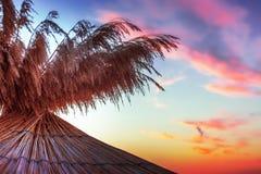 Vivid sunrise on a beautiful sandy beach with sunshade Stock Image