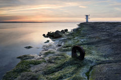 Vivid sunrise over pier and lighthouse in Swinoujscie, Poland. Stock Image