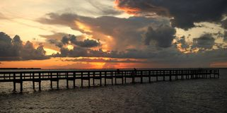 Vivid sunset. A vivid, dramatic sunset over the fishing pier in Gilchrist Park, Punta Gorda Florida stock image