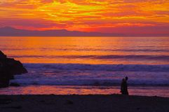 Vivid Sunset, Ventura, California. A vivid sunset over the Santa Barbara Channel with Santa Cruz Island in the background and a couple on the beach in the Stock Photography
