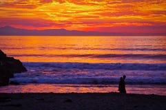 Vivid Sunset, Pacific Ocean, Ventura, California. A couple enjoys a vivid sunset over the Santa Barbara Channel, Pacific Ocean, with Santa Cruz Island in the Stock Image