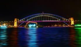 Vivid Sydney- boats cruise by Sydney Harbour Bridge in colour. SYDNEY, AUSTRALIA - MAY 21, 2015; Sydney Harbour Bridge Vivid lights preview for Vivid Sydney 2015 Stock Images