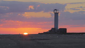 Vivid time lapse of sun setting behind a breakwater. With a lighthouse stock video footage