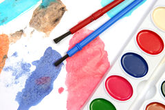 Vivid watercolors. Watercolors and brushes on a painted background Stock Photos