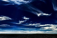 Vivid white Cirrus cloud in dark blue sky. A Vibrant and vivid sky cloudscape with white coloured wispy Cirrus clouds in a dark blue sky. Beauty in nature. New stock photo