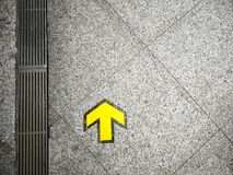 Vivid Yellow Arrow Traffic Sign on the Walkway. Vibrant Yellow Arrow Traffic Sign on the Walkway Royalty Free Stock Image