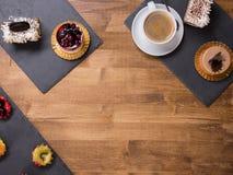 Viwe supérieur d'une tasse de café avec différents gâteaux avec différentes saveurs au-dessus d'une table en bois photos libres de droits