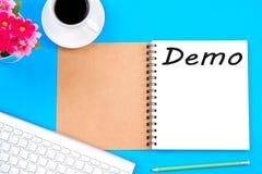 Viwe supérieur de lieu de travail moderne et de mot de démo sur le carnet avec le fond bleu photo libre de droits