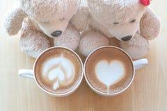 Viwe superior de dois ursos de peluche e copos de café na tabela de madeira do pinho Fotos de Stock Royalty Free