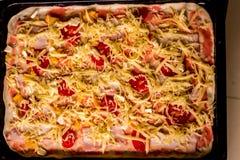Viwev superior de la pizza cruda con el queso, el tomate y las salchichas listos para cocer fotos de archivo
