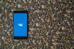 Vkontakte-Logo auf Smartphone auf Hintergrund von kleinen Steinen Stockbild