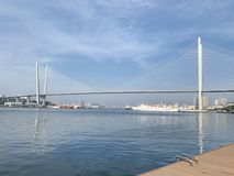 Vladivostok. Golden bridge over Golden horn Bay in may morning and fragment of the embankment of Tsarevic. Vladivostok. Golden bridge — cable-stayed royalty free stock images