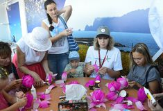 Vladivostok, Russia, September, 10, 2017. People taking part in master class `How to make a Lotus flower from the paper` on the p stock photo