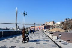 Vladivostok, Rusia, el 19 de enero de 2019 Mujer con un cochecito que camina a lo largo del terraplén del Príncipe heredero Tsesa imagen de archivo libre de regalías