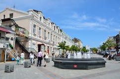Vladivostok, Rusia, junio, 01, 2016 Gente que camina en la calle de almirante Fokin y que habla en los teléfonos celulares fotos de archivo libres de regalías