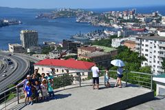 Vladivostok, Russia, August, 30,2018. Tourists looking for summer Vladivostok from the observation deck Eagle`s nest in sunnny day. Vladivostok, Russia. Tourists stock images