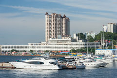 Vladivostok, Russia - circa August 2014: Sailing boats and high rise residential buildings in Vladivostok,  Russia Stock Image