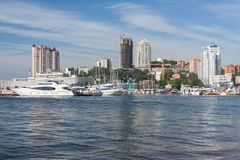 Vladivostok, Russia - circa August 2014: Sailing boats and high rise residential buildings in Vladivostok, Russia royalty free stock images