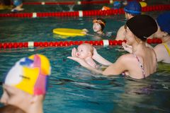 VLADIVOSTOK, RUSSIA-JANUARY 16, 2016 young moms and dads teach babies to swim in the pool. Group lesson. stock photo