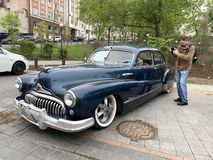 Vladivostok, Russia, May, 18, 2019. Exhibition of American retro-cars. Man photographer  Buick Road Master 1950 year of manufactur. Vladivostok, Russia royalty free stock image