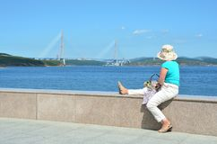 Vladivostok, Russia, September, 10, 2017. Middle-aged woman sitting on the parapet of the promenade in FEFU and looking at the bri. Vladivostok, Russia, middle royalty free stock photo