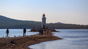 Tokarevsky lighthouse and people visitors during an international sailing regatta against the background of the Russian island of stock photos