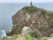 Vladivostok, Russia, June, 02, 2019. Tourists hiking on island of Shkot in cloudy weather near old lighthouse. Vladivostok, Russia. Tourists hiking on island of stock images