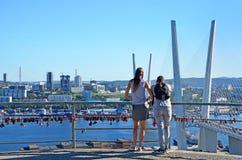 Vladivostok Ryssland, Augusti, 31, 2017 Grabben med flickan som beundrar denblivna bron över Zolotoyen Rog Bay i Septem royaltyfri fotografi