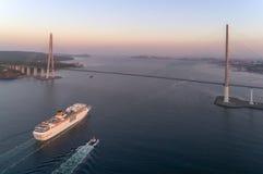 Vladivostok Ryssland - Maj 30, 2017: Det vita kryssningskeppet Costa NeoRomantica passerar under den ryska bron Arkivbilder