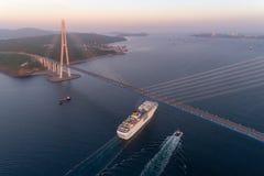 Vladivostok Ryssland - Maj 30, 2017: Det vita kryssningskeppet Costa NeoRomantica passerar under den ryska bron Arkivfoto