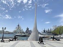 Vladivostok Ryssland, Maj, 21, 2019 Två sjömän som går nära monumentet till grundarna av staden på den skeppKarabelnaya emen royaltyfri foto