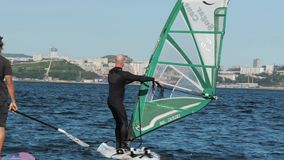 Vladivostok Ryssland - September 1, 2018: Mannen lär att rida på ett bräde med seglar, surfingen Rolig ytterlighet för sommar arkivfilmer